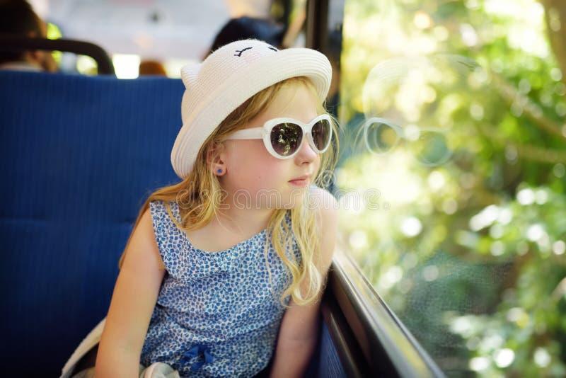 Leuk jong meisje die door trein op de zomerdag reizen Kindzitting door het venster van spoorwagon en buiten het kijken royalty-vrije stock fotografie