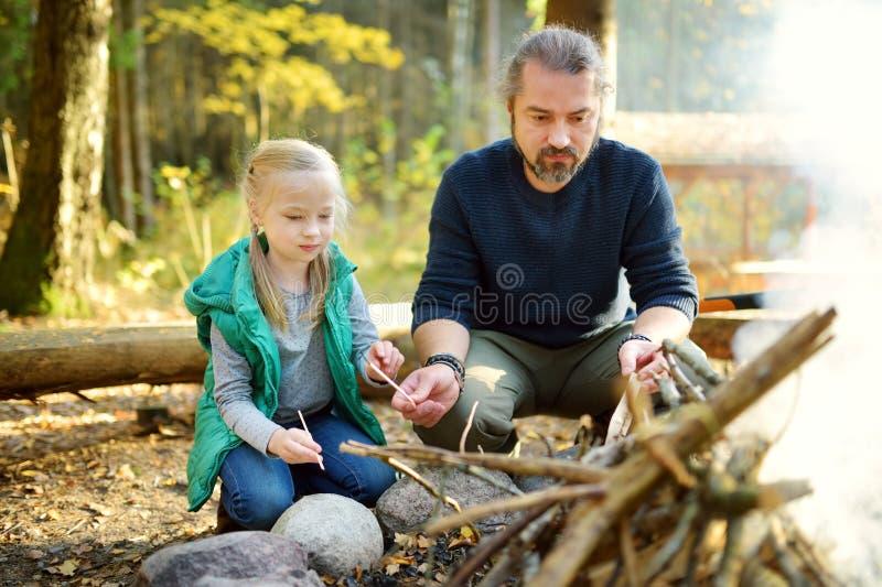 Leuk jong meisje die een vuur leren te beginnen Vader die haar dochter onderwijzen om een brand te maken Kind die pret hebben bij stock foto
