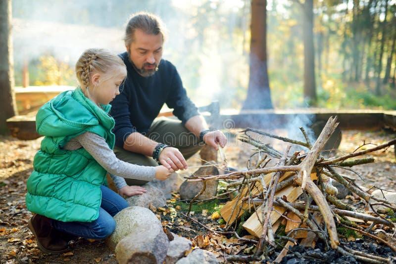 Leuk jong meisje die een vuur leren te beginnen Vader die haar dochter onderwijzen om een brand te maken Kind die pret hebben bij royalty-vrije stock fotografie