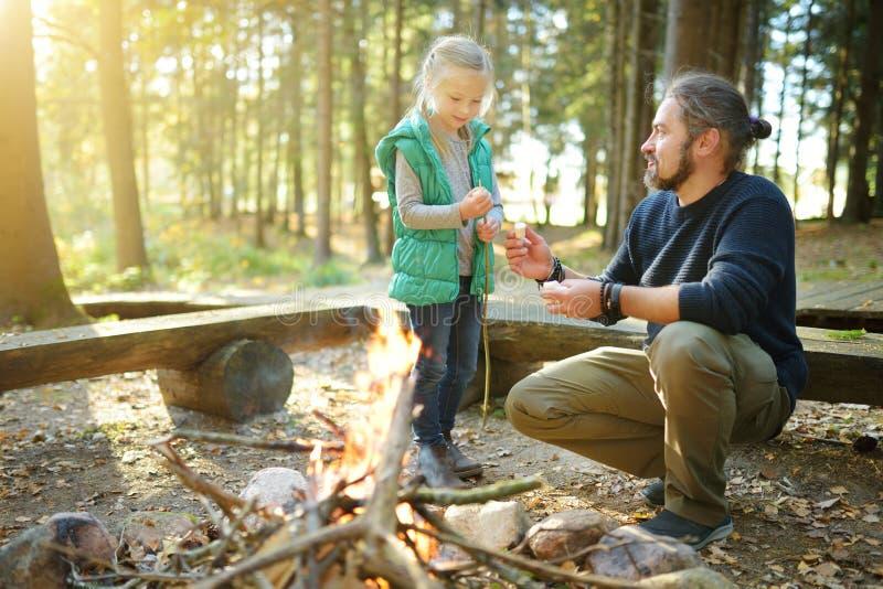Leuk jong meisje die een vuur leren te beginnen Vader die haar dochter onderwijzen om een brand te maken Kind die pret hebben bij stock afbeelding