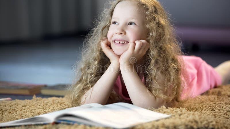 Leuk jong meisje die over gelukkige toekomst dromen, die op zacht tapijt thuis liggen stock fotografie