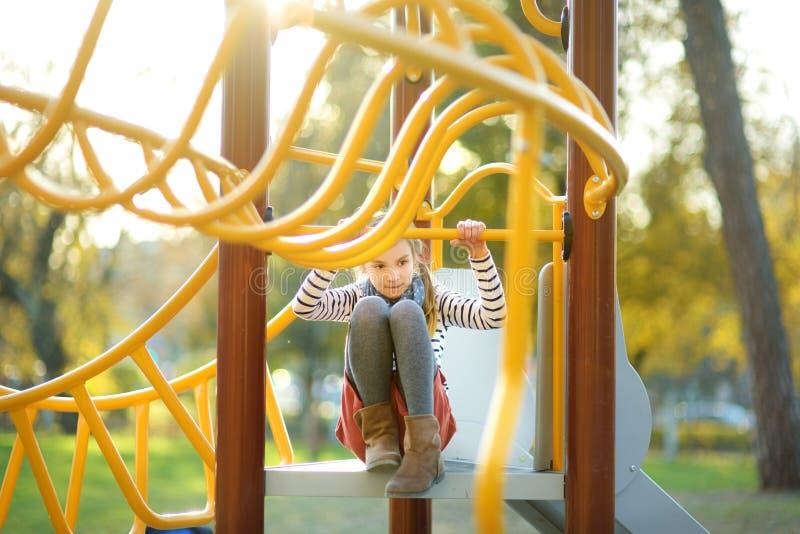 Leuk jong meisje die pret op een speelplaats in openlucht in de zomer hebben stock afbeelding