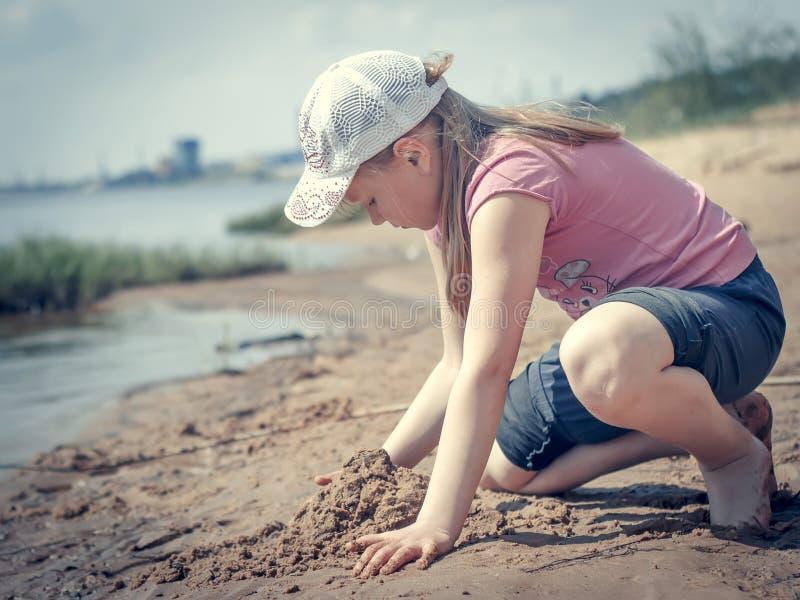 Leuk jong meisje die pret op een zandig meerstrand hebben op warme en zonnige de zomerdag Het jonge meisje spelen door de rivier  stock afbeelding