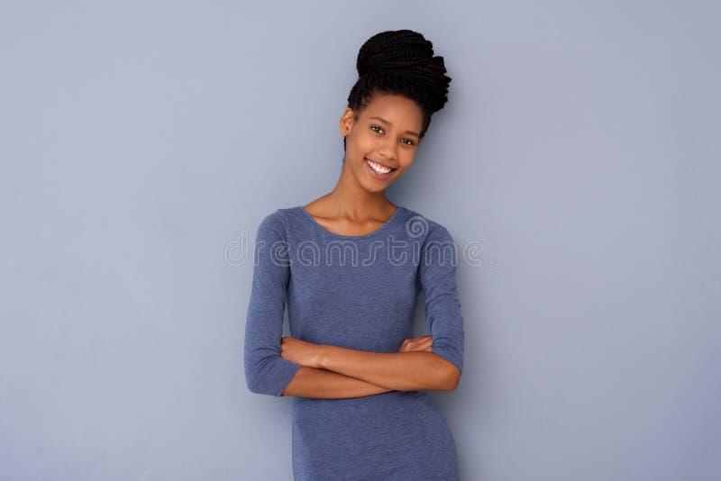 Leuk jong meisje die zich met gekruiste wapens bevinden en tegen grijze achtergrond glimlachen stock afbeeldingen