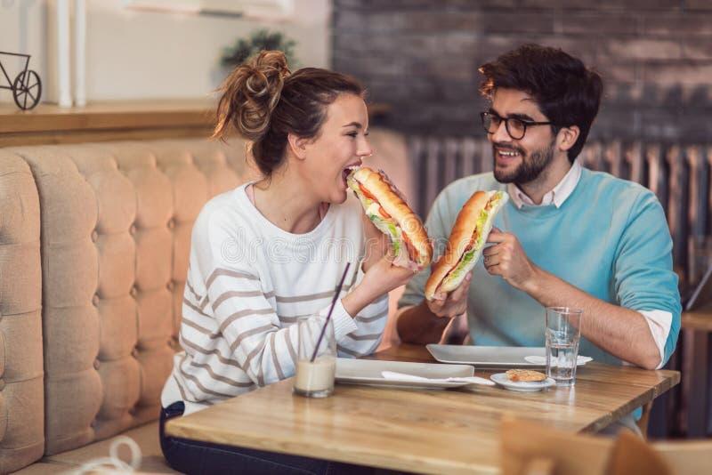 Leuk jong paar die een goede tijd hebben samen en voedsel in koffie eten stock afbeeldingen