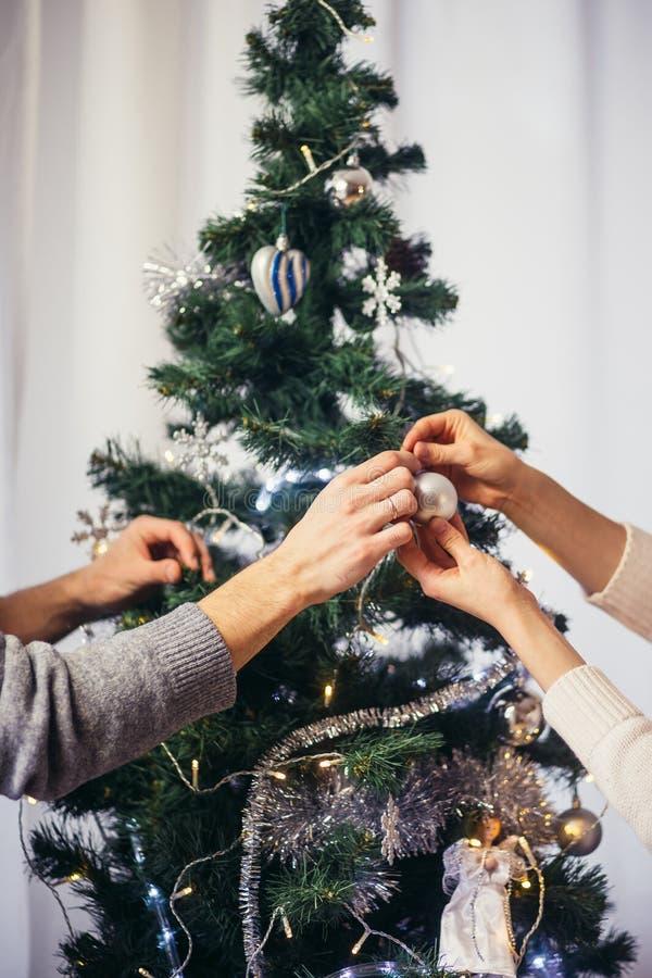 Leuk, jong paar die een Kerstboom verfraaien stock fotografie