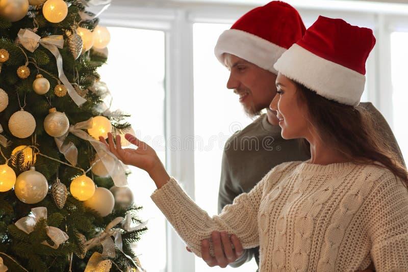 Leuk jong paar die in Kerstmanhoeden Kerstboom thuis verfraaien royalty-vrije stock afbeeldingen