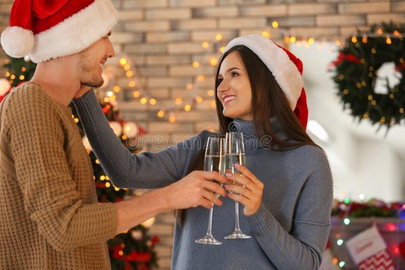 Leuk jong paar met glazen van champagne het vieren Kerstmis thuis royalty-vrije stock fotografie