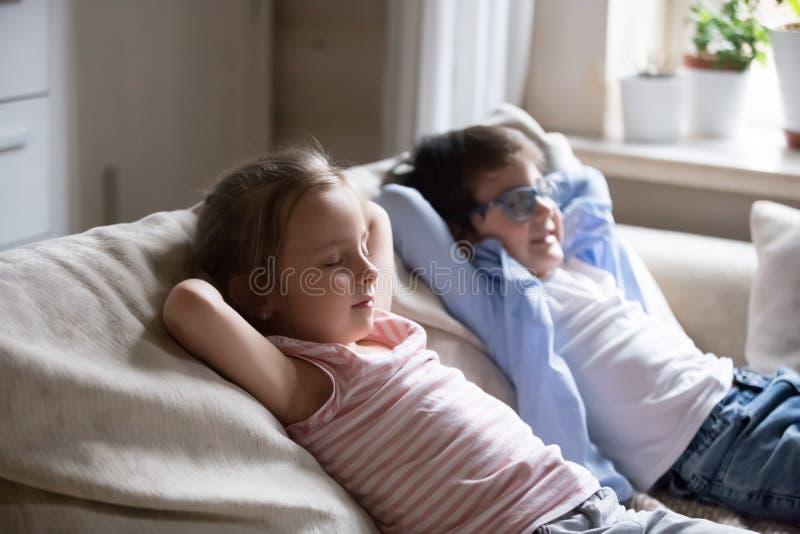 Leuk jongen en meisje die bij het comfortabele bank ontspannen liggen stock foto
