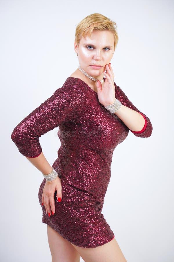 Leuk Kaukasisch curvy meisje met kort blondehaar en plus groottelichaam dat de mooie elegante kleding van de kersenkleur met love royalty-vrije stock foto
