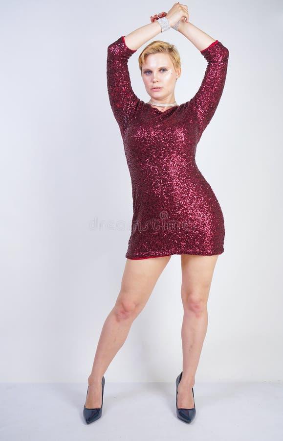 Leuk Kaukasisch curvy meisje met kort blondehaar en plus groottelichaam die de mooie elegante kleding van de kersenkleur met love royalty-vrije stock afbeelding