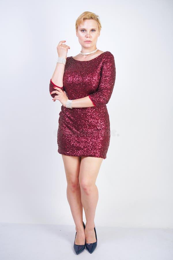 Leuk Kaukasisch curvy meisje met kort blondehaar en plus groottelichaam die de mooie elegante kleding van de kersenkleur met love stock fotografie