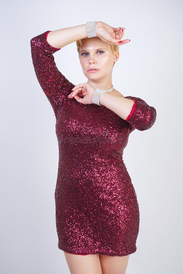 Leuk Kaukasisch curvy meisje met kort blondehaar en plus groottelichaam die de mooie elegante kleding van de kersenkleur met love stock afbeelding