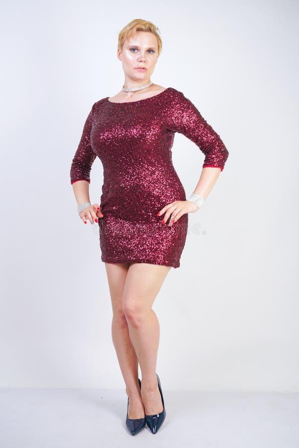 Leuk Kaukasisch curvy meisje met kort blondehaar en plus groottelichaam die de mooie elegante kleding van de kersenkleur met love royalty-vrije stock foto