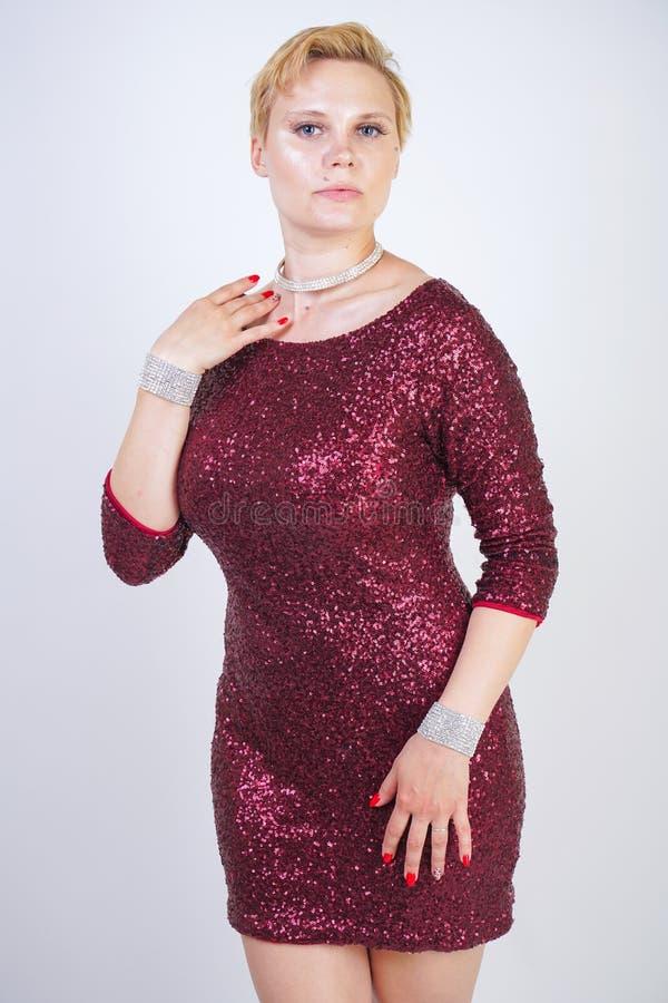 Leuk Kaukasisch curvy meisje met kort blondehaar en plus groottelichaam die de mooie elegante kleding van de kersenkleur met love royalty-vrije stock fotografie