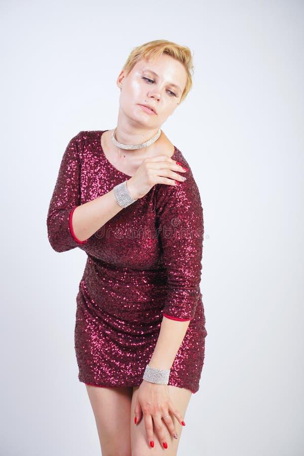 Leuk Kaukasisch curvy meisje met kort blondehaar en plus groottelichaam die de mooie elegante kleding van de kersenkleur met love stock foto's