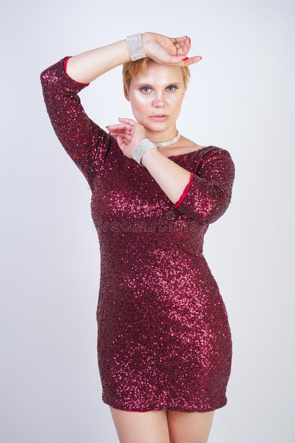 Leuk Kaukasisch curvy meisje met kort blondehaar en plus groottelichaam die de mooie elegante kleding van de kersenkleur met love stock afbeeldingen