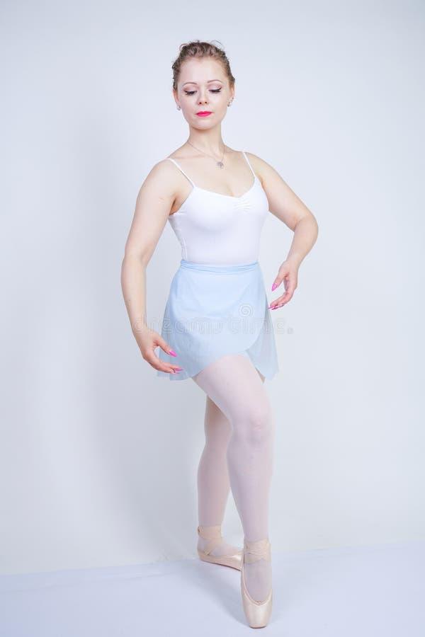 Leuk Kaukasisch meisje die in balletkleren een ballerina op een witte achtergrond in de Studio leren te zijn plus dromen van de g stock afbeelding