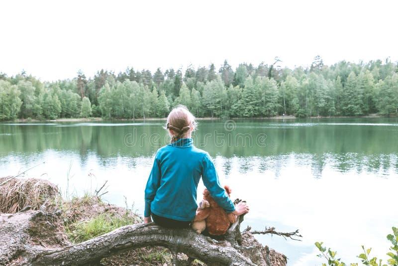 Leuk Kaukasisch meisje op het meer met haar pluchespeelgoed, teddybeer en konijntje Achter mening stock foto
