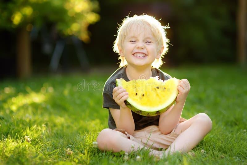 Leuk Kaukasisch weinig jongen die met blonde haren gele watermeloen in openlucht eten royalty-vrije stock afbeeldingen