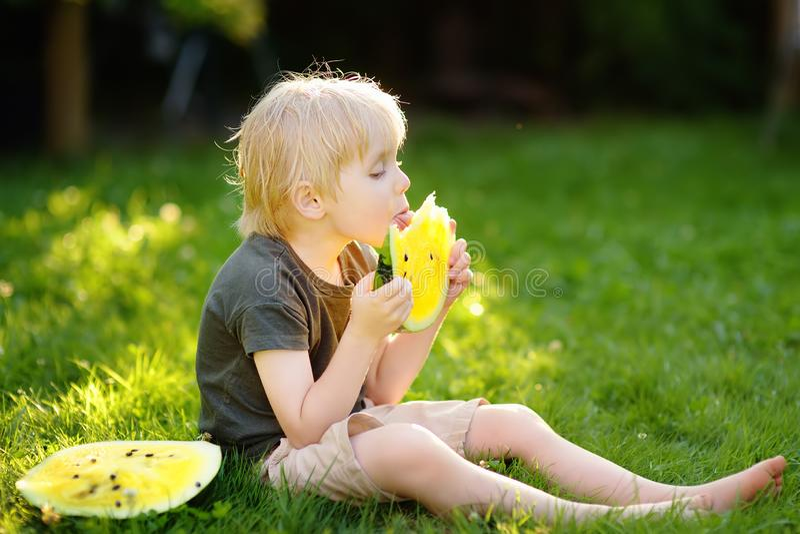Leuk Kaukasisch weinig jongen die met blonde haren gele watermeloen in openlucht eten royalty-vrije stock foto