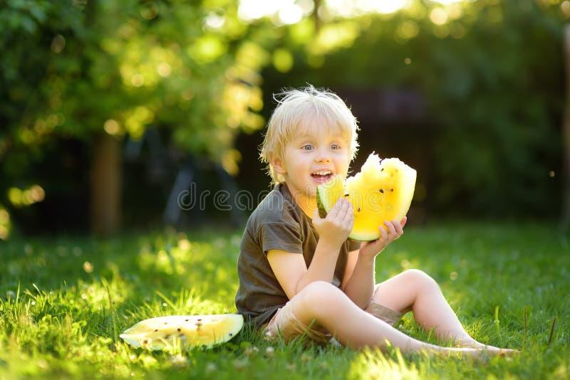 Leuk Kaukasisch weinig jongen die met blonde haren gele watermeloen in openlucht eten stock afbeeldingen