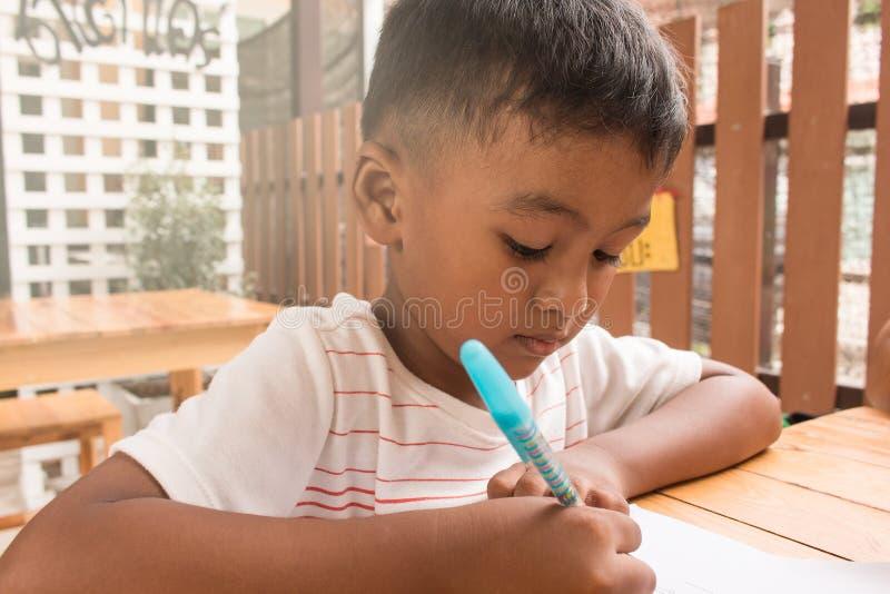 Leuk kind Aziaat weinig jongen die thuiswerk doen royalty-vrije stock afbeelding