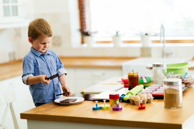 Leuk kind die een chef-kok leren te worden stock foto
