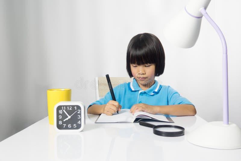 Leuk kind die en aan het werkbureau schrijven werken stock afbeelding