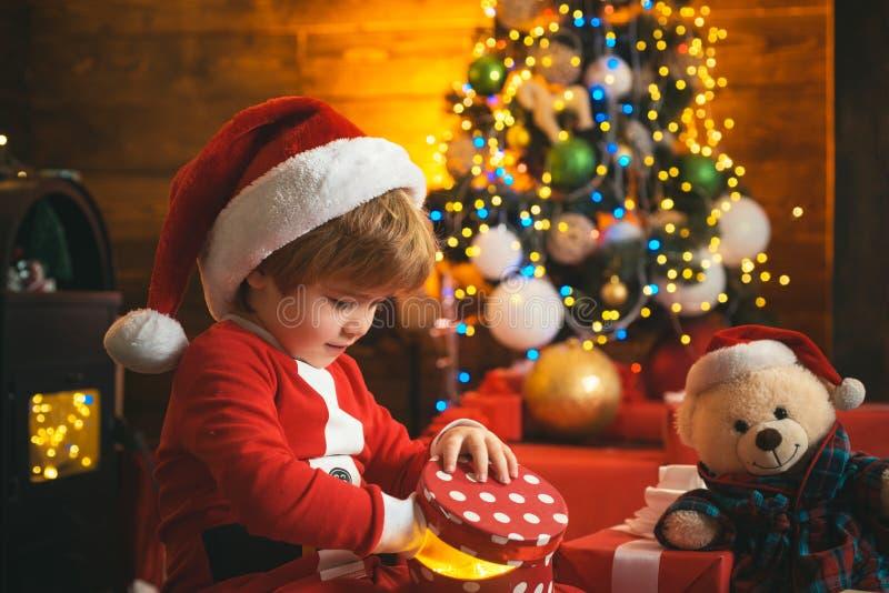 Leuk kind die op het nieuwe jaar wachten, die door de Kerstboom zitten Kerstmisjong geitje Gelukkig weinig glimlachende jongen me royalty-vrije stock foto