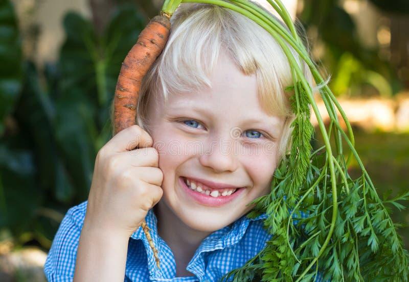 Leuk kind die organische wortel over zijn hoofd houden als haar stock foto
