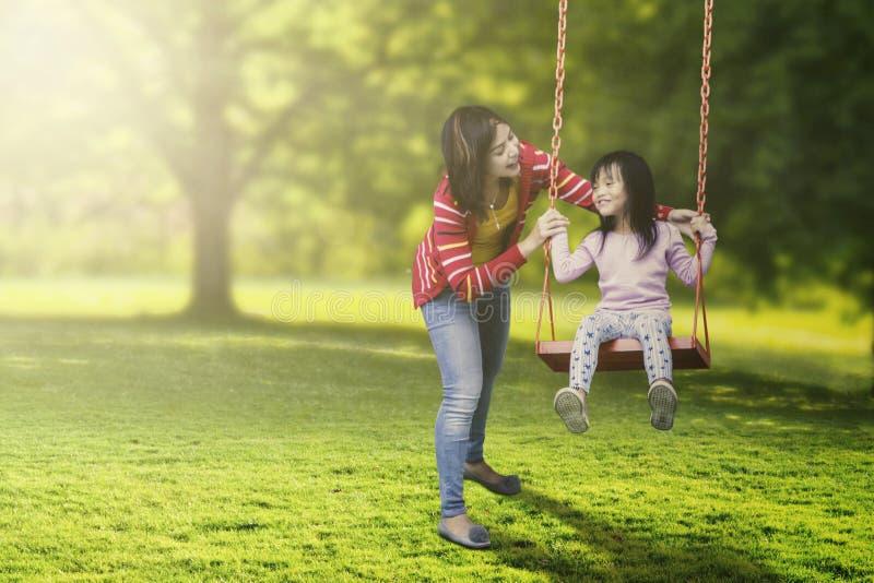 Leuk kind en jonge moeder speelschommeling royalty-vrije stock afbeelding