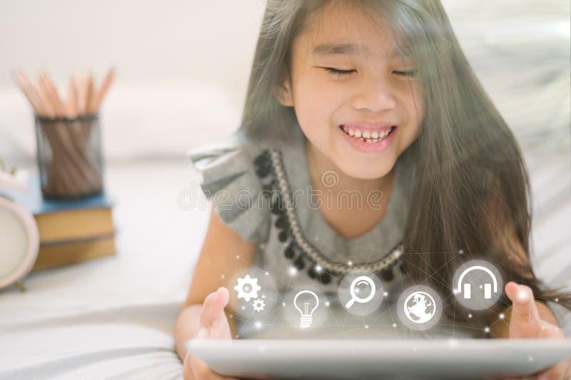 Leuk kind gebruikend een tablet en glimlachend terwijl thuis het zitten op bank stock afbeeldingen