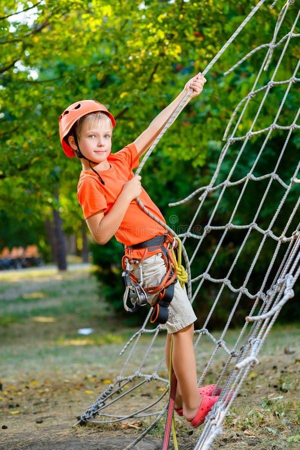 Leuk kind, jongen, die in een kabelspeelplaats beklimmen stock foto's
