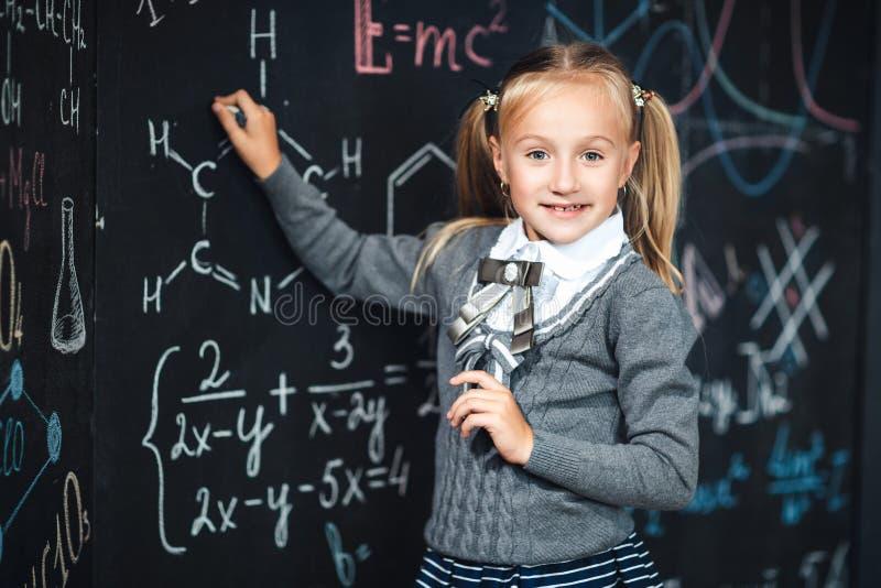 Leuk kind in school het eenvormige trekken op leeg bord met schoolformules op school Ga voor het eerst naar school kid royalty-vrije stock afbeeldingen