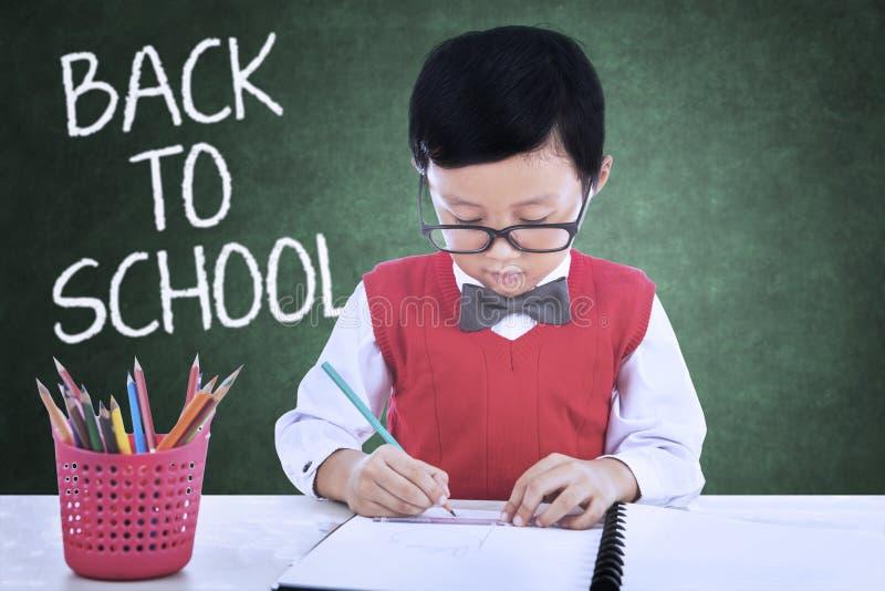 Leuk kind terug naar school en tekening in klasse royalty-vrije stock foto's