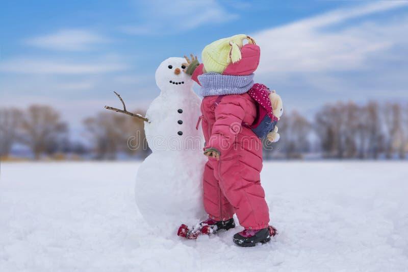 Leuk kindmeisje die sneeuwman maken op heldere sneeuwplaats De winter openluchtactiviteiten royalty-vrije stock afbeelding