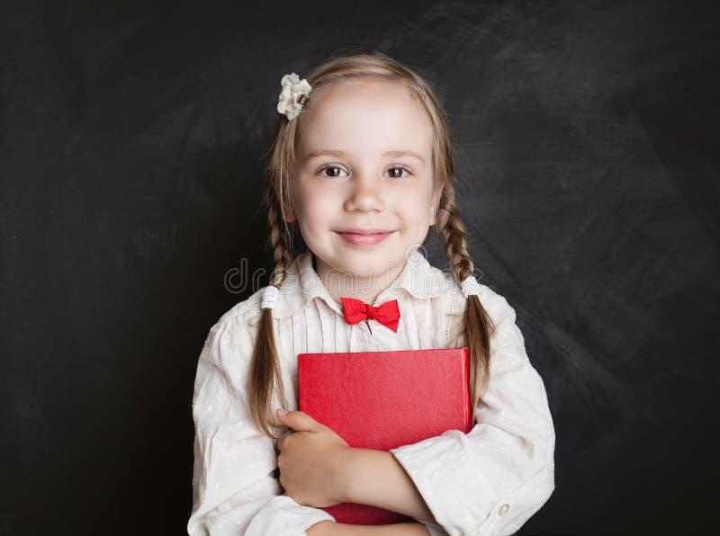 Leuk kindmeisje met boek die pret op bord hebben royalty-vrije stock afbeelding
