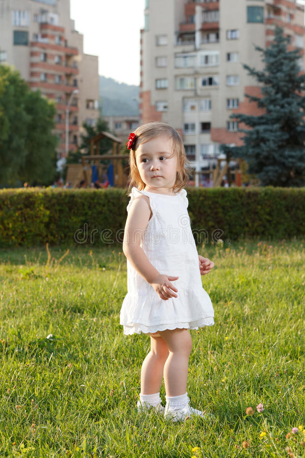 Leuk klein meisje die zich in gras bevinden stock fotografie