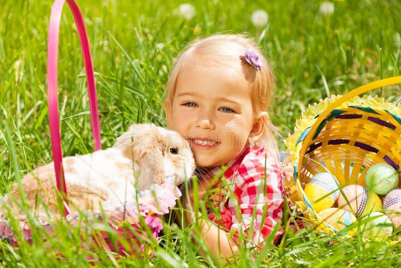 Leuk klein meisje geknuffelkonijn op gebied stock foto's