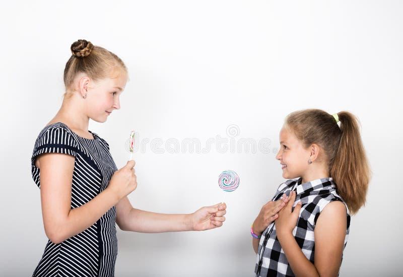 Leuk klein meisje twee die heldere lollys eten Grappige Jonge geitjes De beste vrienden vertroetelen en stellend royalty-vrije stock foto's