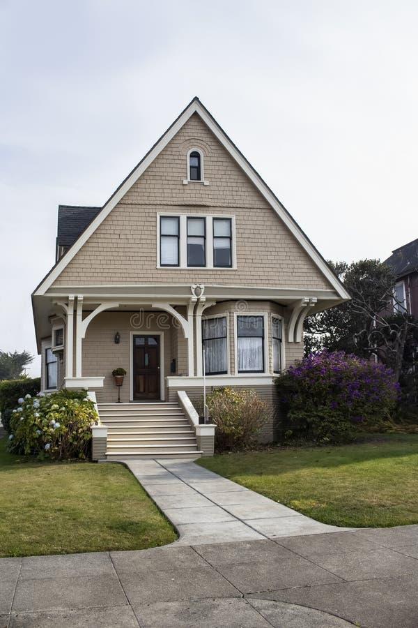 Leuk klein Victoriaans huis met dakspaan het opruimen en erker en bloemen in de yard stock fotografie