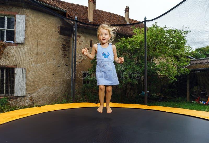 Leuk kleutermeisje die op trampoline springen royalty-vrije stock foto