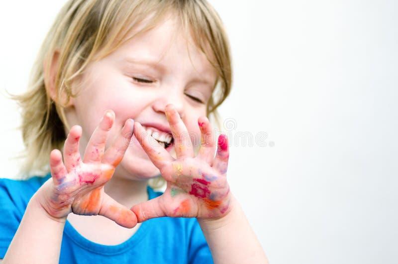 Leuk kleutermeisje met glimlach die gekleurde handen tonen Selectiv stock fotografie