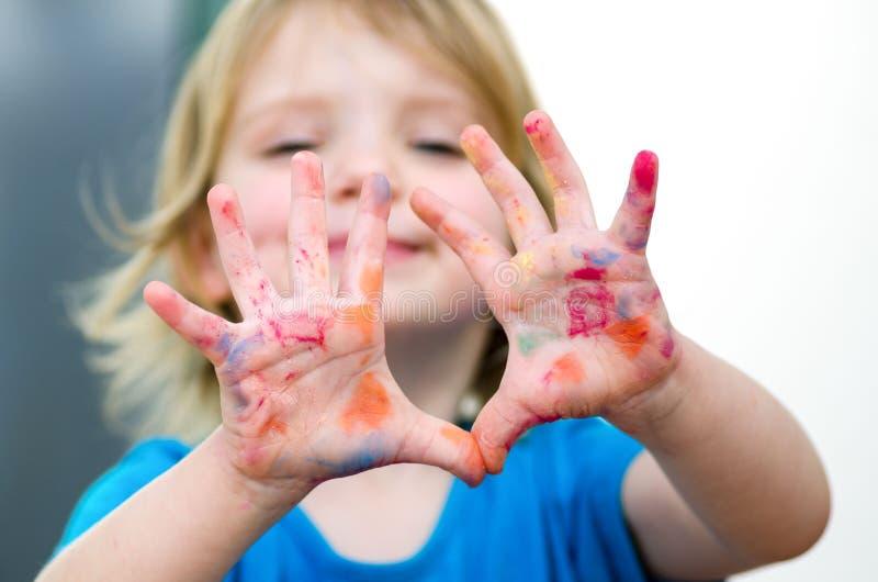 Leuk kleutermeisje met glimlach die gekleurde handen tonen Selectiv royalty-vrije stock foto's