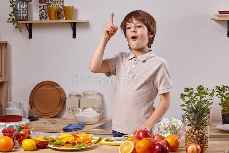 Leuk kookt weinig jongen met bruin haar bij een keuken tegen een witte muur met planken op het stock afbeeldingen