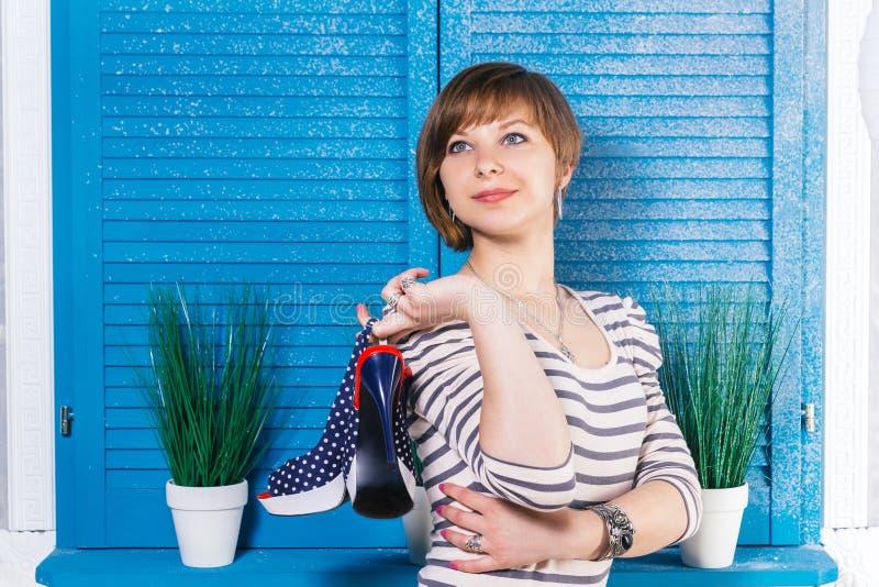 Leuk kortharig tienermeisje die haar nieuwe hoog gehielde schoenen voor blauw jaloezievenster houden met groene installaties Het  stock fotografie
