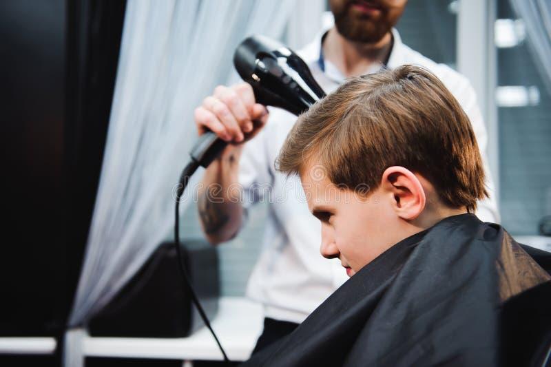 Leuk krijgt weinig jongen kapsel door kapper bij de herenkapper royalty-vrije stock afbeeldingen