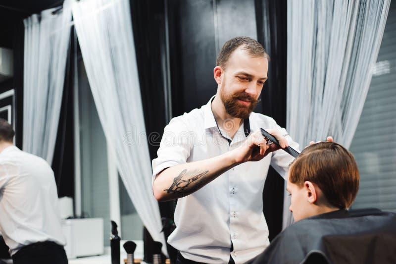 Leuk krijgt weinig jongen kapsel door kapper bij de herenkapper stock foto