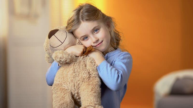 Leuk krullend-haired blond meisje dat teddybeer koestert en bij camera, geluk glimlacht stock afbeelding